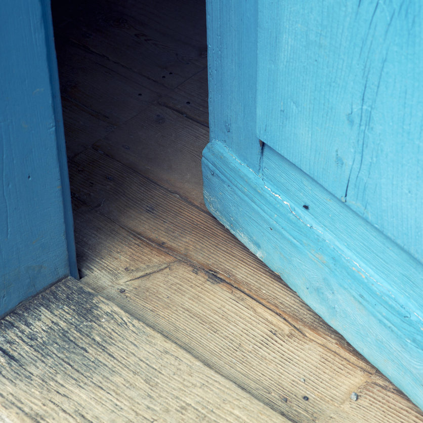 closeup of an open old blue wooden door
